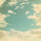 Old paper background with blue sky. And white clouds in grunge style Royalty Free Stock Photos