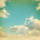 Old paper background with blue sky. And white clouds in grunge style Royalty Free Stock Image