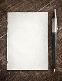 Old paper and ballpen. On wooden board Royalty Free Stock Photography