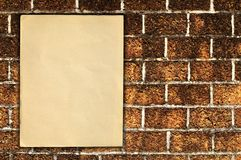 Old paper on brick wall Royalty Free Stock Images