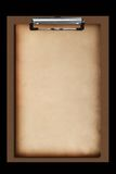 Old paper on brown clipboard. On black background Royalty Free Stock Photo