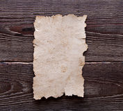 Old paper on brown wood texture Royalty Free Stock Photo