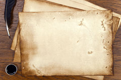 Old paper on brown wood texture with feather and ink Royalty Free Stock Image
