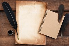 Old paper on brown wood texture with feather and ink, blank notebook Stock Images