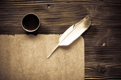 Old paper on brown wood texture with feather and ink Royalty Free Stock Photo