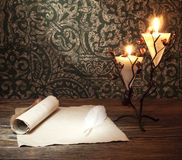 Old paper with a candle and a quill pen Royalty Free Stock Image