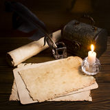 Old paper and a candle on a wooden table Stock Photos