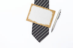 Old paper card on necktie with new silver pen on white background Stock Images