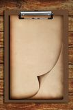Old paper on clip board. With wooden table background Stock Photos
