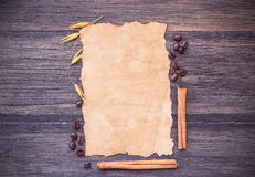 Old paper and coffee beans on dark wooden table background. Royalty Free Stock Photo