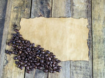 Old paper and coffee beans on wooden table Royalty Free Stock Image