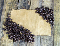 Old paper and coffee beans on wooden table Royalty Free Stock Photos