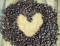 Old paper and coffee beans on wooden table Stock Photography