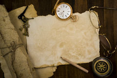 Old paper, compass, pocket watch on wooden background Royalty Free Stock Images