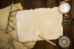Old paper, compass, pocket watch on wooden background Stock Photos