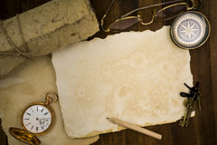 Old paper, compass, pocket watch on wooden background Royalty Free Stock Image