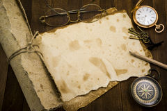 Old paper, compass, pocket watch on wooden background Royalty Free Stock Photo