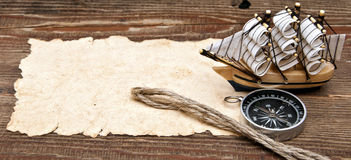 Old paper, compass, rope and model classic boat. On wood background stock photography