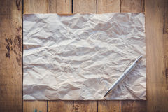 Old paper crumpled and pen on wood background Royalty Free Stock Photos