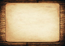 Old paper on dark wooden wall Stock Photos