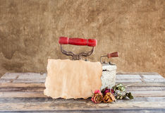 Old paper with dried rose and rusty iron on wooden background Stock Image
