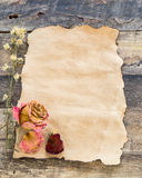 Old-paper with dried rose on a wooden background Stock Photography