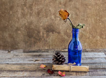 Old paper with dry rose on wooden background Stock Photo