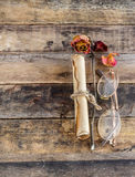 Old paper with dry rose on wooden background Royalty Free Stock Image
