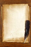 Old paper with feather on brown wood texture Royalty Free Stock Photo