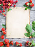 Old paper with fresh strawberries and raspberries on wooden table. Healthy eating concept.  Old paper with fresh strawberries and raspberries on wooden table Stock Photos