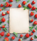 Old paper with fresh strawberry and  mint leaf on wooden table. Royalty Free Stock Photo