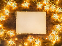 Old paper with garland on wooden background. Royalty Free Stock Photography