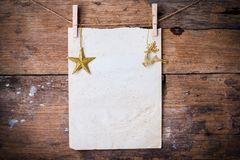 Old paper and golden star with a pin. Against the dark old brown wooden background stock image
