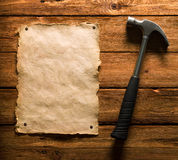 Old Paper and Hammer. A hammer and an old paper nailed on a wooden surface Royalty Free Stock Photo
