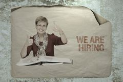 We are hiring. Old paper job ad on a cement wall with a portrait of a staff member showing ok signs by her hands. busines recruitment concept Stock Photo