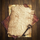 Old paper and key on wooden background Royalty Free Stock Photography
