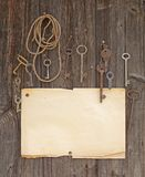 Old paper and keys. On brown wood texture with natural patterns Royalty Free Stock Photo