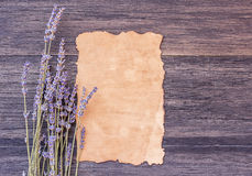 Old paper and lavender flower on dark wooden table background Royalty Free Stock Images