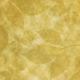 Old paper with leaves. Golden parchment paper with leaves imprinted on it royalty free illustration