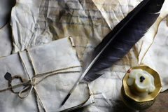 Old paper letter and black feather. On wooden table Stock Image