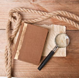 Old paper and magnifier. Rope, book, old paper and magnifying glass on a wooden background Stock Images