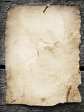 Old paper nailed to a wooden background Royalty Free Stock Photos