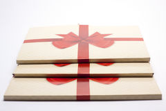 Old paper packing with red ribbon and red bow Stock Photos