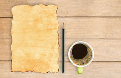 Old paper and pencil with coffee cup on wood table. Royalty Free Stock Photo