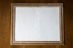Old paper photo frame. Blank old paper photo frame on wooden background Royalty Free Stock Image