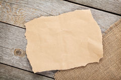 Old paper piece and burlap on wooden textured background Stock Image