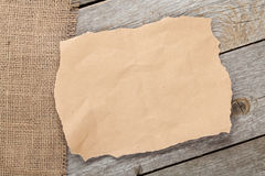 Old paper piece and burlap on wooden textured background Stock Photos