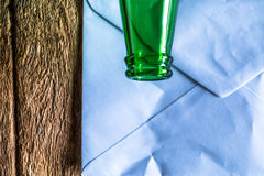 Old paper is placed on the table with a bottle of empty wine pla. Ced together royalty free stock images