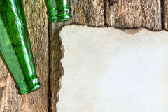 Old paper is placed on the table with a bottle of empty wine pla. Ced together royalty free stock image