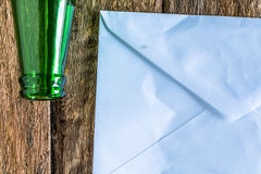 Old paper is placed on the table with a bottle of empty wine pla. Ced together royalty free stock photography